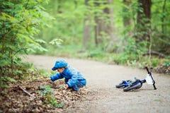 Niño caucásico del niño pequeño en chaqueta azul, vaqueros y gorra de béisbol con la bici en patio del parque afuera, sentándose  Fotografía de archivo