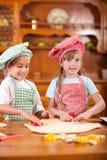 Niño caucásico hermoso dos que hace una torta, sonriendo feliz, foto de archivo libre de regalías