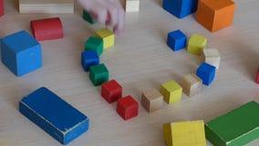 Niño caucásico que juega con los ladrillos de madera