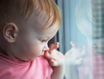 Niño cerca de la ventana Foto de archivo libre de regalías