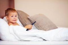 Niño, cogido en ver la TV prohibida Imagen de archivo