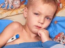 Niño con alta fiebre imagenes de archivo