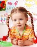 Niño con drenaje de la tiza en sala de juegos. imagenes de archivo