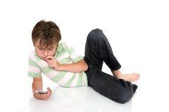 Niño con el adminículo electrónico imagen de archivo