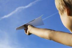 Niño con el avión de papel contra el cielo azul Opinión de ángulo bajo Imagen de archivo libre de regalías
