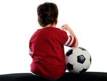 Niño con el balón de fútbol que se sienta cómodamente Foto de archivo libre de regalías