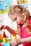 Niño con el bloque en sitio del juego. Desarrollo. Imagen de archivo