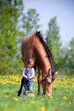 Niño con el caballo de la castaña en campo Imagen de archivo