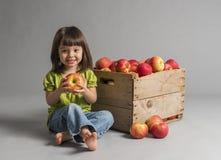 Niño con el cajón de manzanas Fotografía de archivo