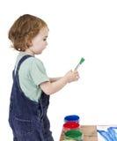 Niño con el cepillo y la pintura verde imagenes de archivo