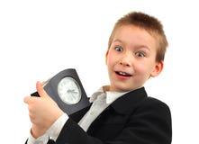 Niño con el despertador Foto de archivo libre de regalías