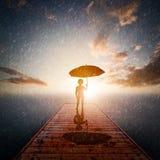 Niño con el embarcadero de madera solo permanente del paraguas en la lluvia que mira el mar imagen de archivo libre de regalías