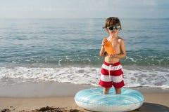 Niño con el espray de la protección del sol debajo del flotador Imágenes de archivo libres de regalías