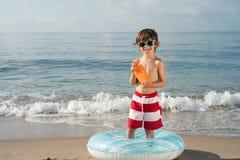 Niño con el espray de la protección del sol en la playa Fotografía de archivo libre de regalías