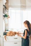 Niño con el gato en la cocina Fotos de archivo libres de regalías