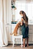 Niño con el gato en la cocina Foto de archivo