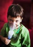 Niño con el inhalador de los aerosoles Fotos de archivo libres de regalías