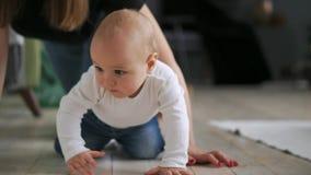 Niño con el juguete en la boca que se arrastra en el sofá Ciérrese para arriba del bebé desnudo en pañales que camina en cama con almacen de video