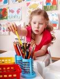 Niño con el lápiz del color en pre-entrenamiento. imagenes de archivo