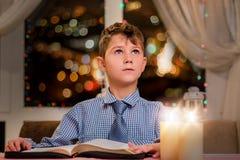 Niño con el libro que mira para arriba Fotografía de archivo libre de regalías