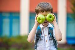 Niño con el libro y la manzana verde al aire libre foto de archivo libre de regalías