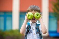 Niño con el libro y la manzana verde al aire libre Imagen de archivo