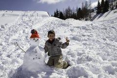 Niño con el muñeco de nieve Imágenes de archivo libres de regalías