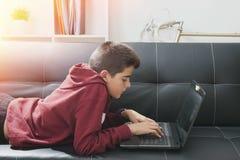 Niño con el ordenador portátil del ordenador Fotografía de archivo