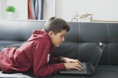 Niño con el ordenador portátil del ordenador Fotografía de archivo libre de regalías