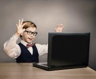 Niño con el ordenador portátil, Little Boy en vidrios sorprendente mirando el ordenador Fotos de archivo
