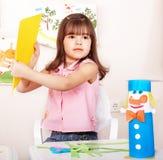 Niño con el papel del corte de las tijeras en pre-entrenamiento. Imágenes de archivo libres de regalías