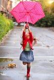 Niño con el paraguas de los lunares que lleva las botas de lluvia rojas Fotos de archivo