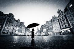 Niño con el paraguas que se coloca solamente en ciudad vieja del guijarro en lluvia Imagen de archivo