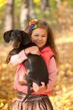 Niño con el perrito del perro basset Imagen de archivo