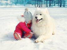 Niño con el perro blanco del samoyedo en la nieve en invierno Foto de archivo