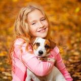 Niño con el perro en el otoño Fotos de archivo