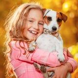 Niño con el perro en el otoño Imagen de archivo
