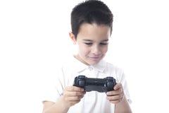 Niño con el regulador del juego en sus manos que miran abajo. Imagenes de archivo
