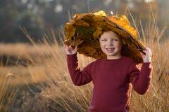 Niño con el sombrero entre las hojas en otoño fotos de archivo libres de regalías