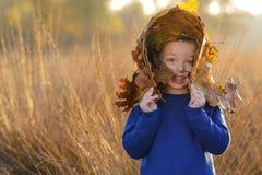Niño con el sombrero entre las hojas en otoño fotografía de archivo
