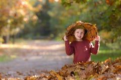 Niño con el sombrero entre las hojas en otoño fotografía de archivo libre de regalías