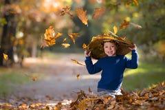 Niño con el sombrero entre las hojas en otoño imágenes de archivo libres de regalías