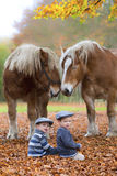 Niño con el sombrero entre las hojas y los caballos en el otoño fotografía de archivo
