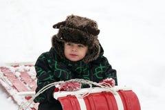 Niño con el sombrero peludo en trineo largo Foto de archivo libre de regalías