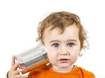 Niño con el teléfono de la lata que mira a la cámara fotografía de archivo