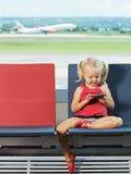 Niño con el teléfono en las manos el aeropuerto imagen de archivo libre de regalías