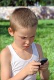 Niño con el teléfono móvil Imagen de archivo libre de regalías
