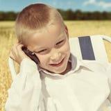 Niño con el teléfono móvil al aire libre Fotos de archivo