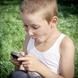 Niño con el teléfono móvil al aire libre Fotografía de archivo libre de regalías