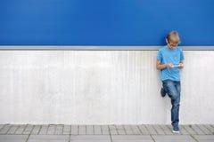 Niño con el teléfono móvil que se coloca cerca de la pared azul y gris afuera Imagen de archivo